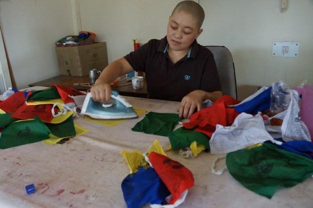 Tibetan Buddhist nun making prayer flags