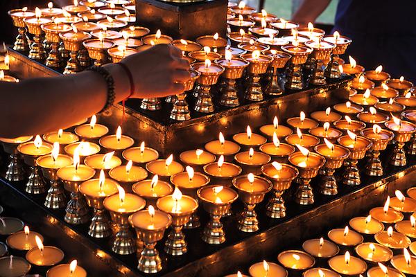 Tibetan Buddhist nuns lighting butter lamps