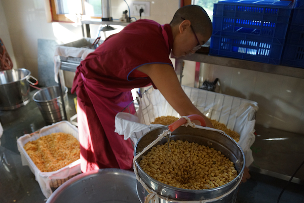 Tibetan Buddhist nun prepares soybeans for making tofu
