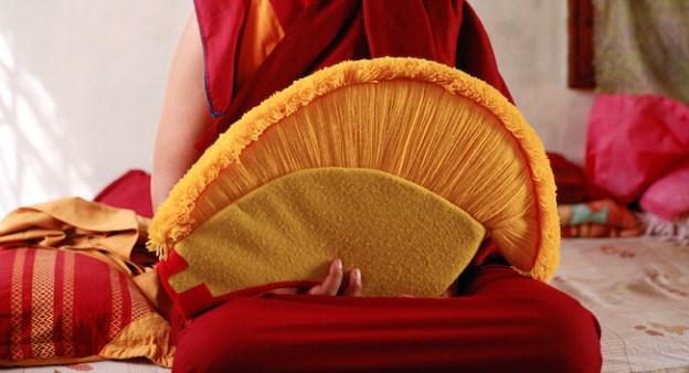 Tibetan Buddhist nun holding Geshema hat