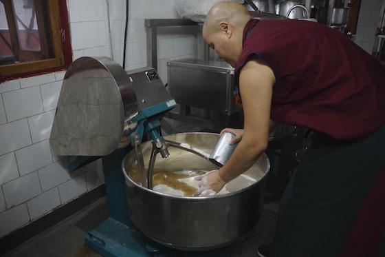 Tibetan Buddhist nun making dough with electric mixer