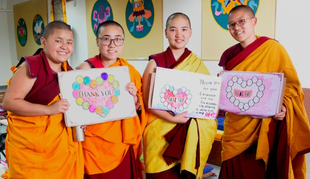 Reports on major projects, Tibetan Buddhist nuns hold thank you signs