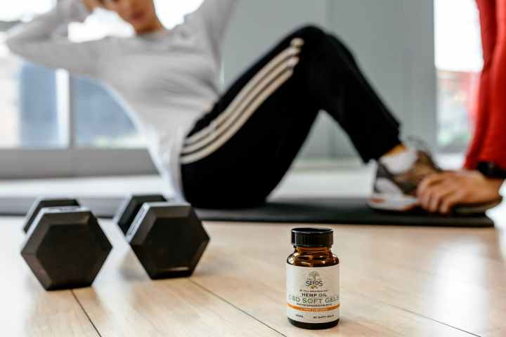 two black dumbbells and brown glass bottle