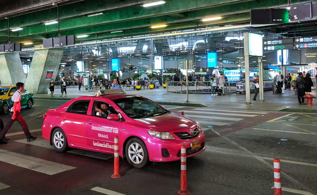 Taxi leaving from Bangkok Airport. The bus ticket counter to get tickets from Bangkok Airport to Pattaya is seen in the background