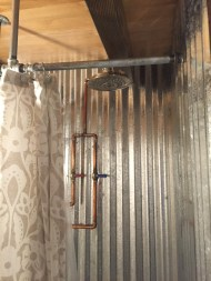 Exposed plumbing, curtain rod and amazing shower head