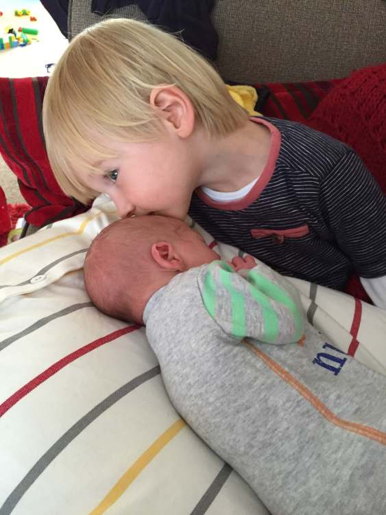 Toby giving newborn Gabe a kiss