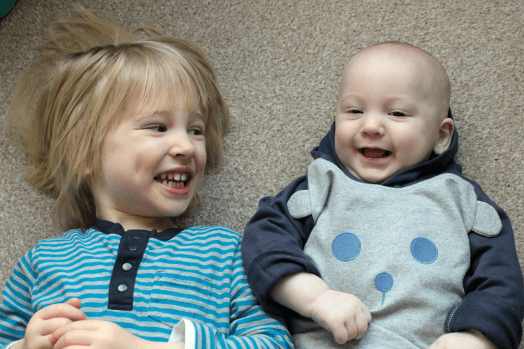 Baby and toddler brothers laughing together