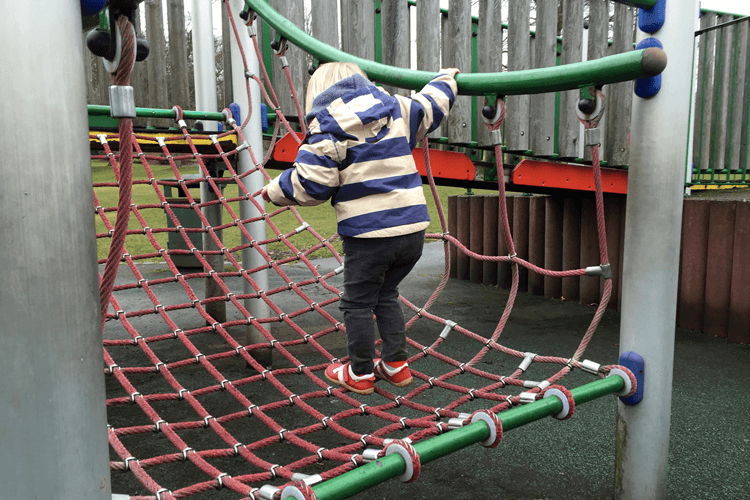 Toddler climbing a cargo net at the park for the first time