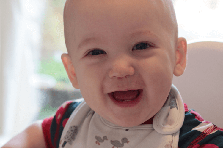 Big smiles and a sore nose at eight months old