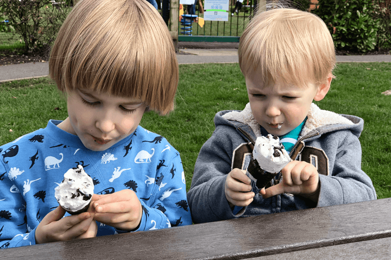 Toby and Gabe looking alike as they eat ice cream at the park