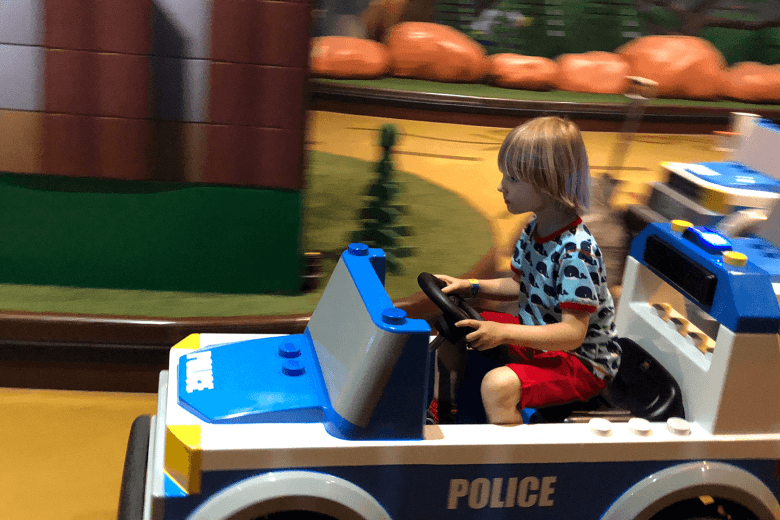 Toby driving a police car at LEGOLAND Discovery Manchester