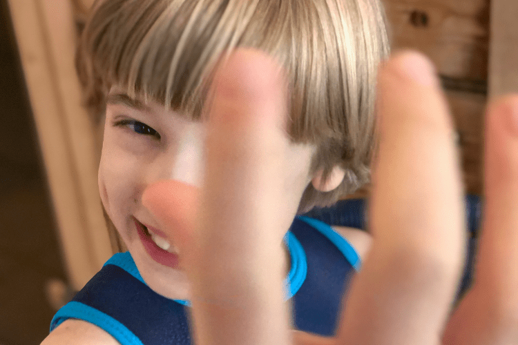 Boy smiling with his hand in front of his face
