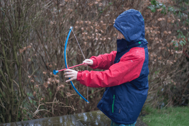 A boy in a navy coat with red sleeves pulling back on a wooden bow and arrow