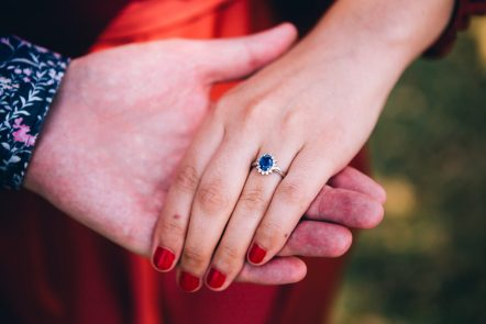 Two hands, one wearing an engagement ring with a blue stone