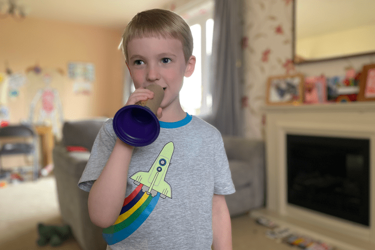Gabe holding a toilet roll tube megaphone in front of his mouth