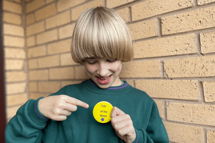 Toby in a green Cub jumper holding a yellow 'Cub of the Week badge