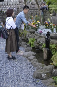 Pouring water to bless and shorten the time children's souls must suffer in the underworld. Kamakura
