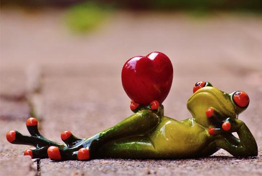 Una figura de una rana tumbada sobre la acera sujetando un corazón.
