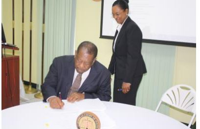 The President of Caribbean Court of Justice, the Right Honourable Sir Dennis Byron (seated), signs the revised rules governing the Original Jurisdiction.  The signing took place on 21 April 2017 at an event held by the Court in celebration of its 12th anniversary.  The CCJ's Registrar and Marshal, Mrs. Jacqueline Graham, who was a part of the review committee, watches as the document is authorised.
