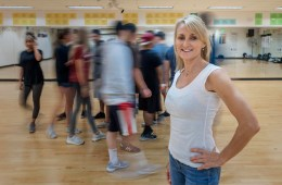 Cathrine Himberg poses while her students move in a blur in the background