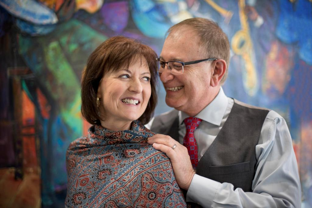Celeste Jones turns her head to smile at Eddie Vela while he has his hands on her shoulders in front of a colorful painting.