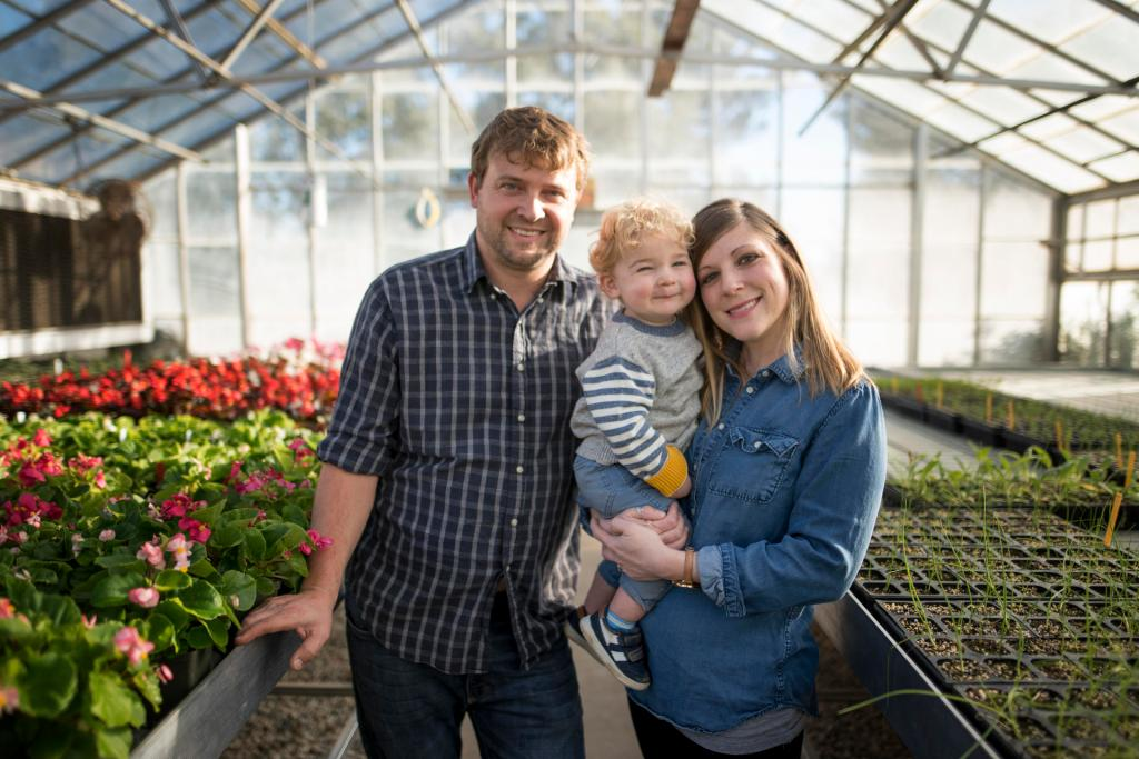 Matt, Ollis, and Lauren Housley stand between rows of flowers and plants in the greenhouse.
