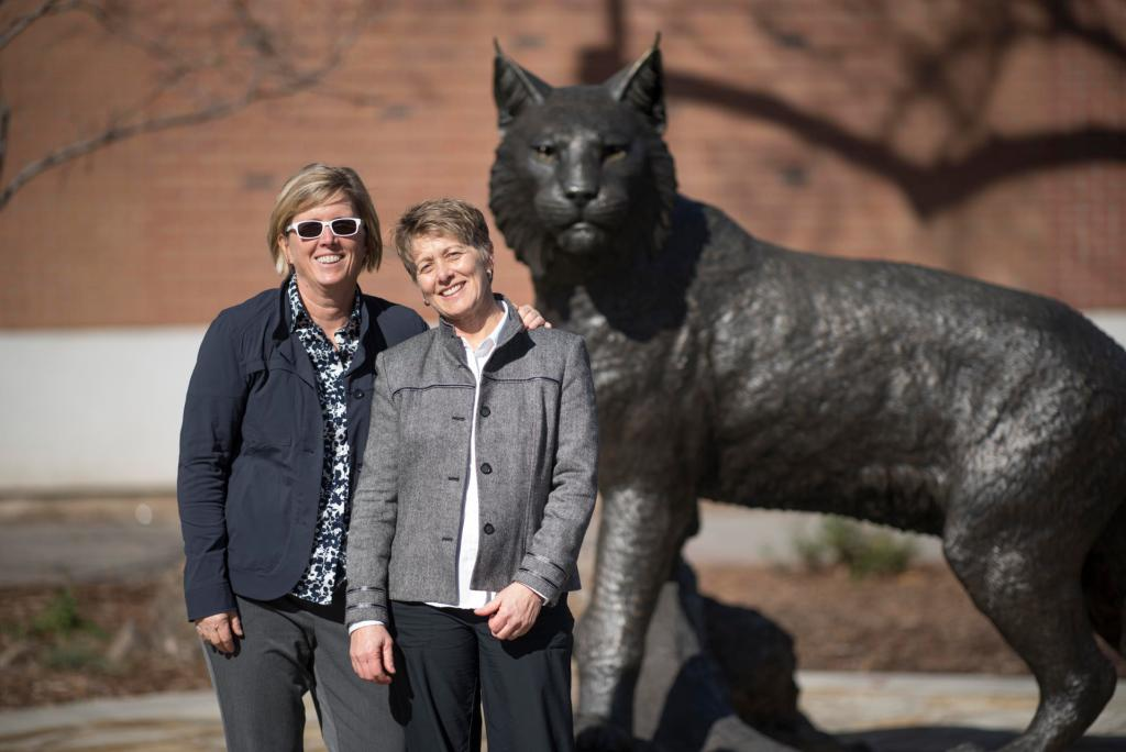 Mary Wallmark holds an arm around Kim Chappell's shoulders as they stand in front of the Wildcat Statue.