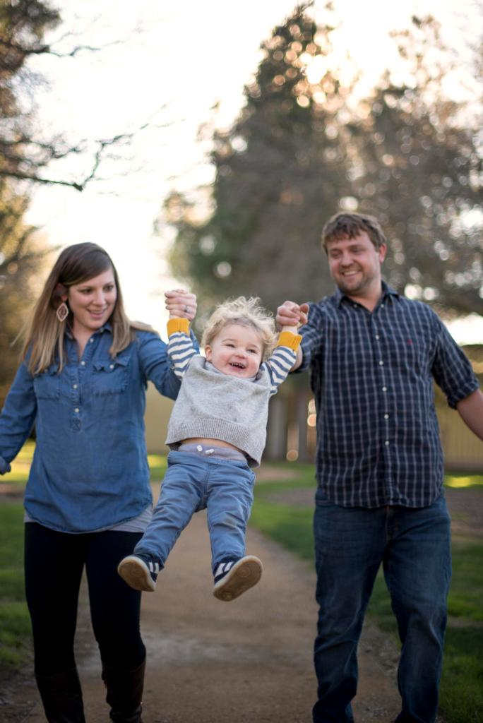 Laure and Matt Housley walk down a dirt path holding the hands of their son Ollis between them and swinging him off the ground.