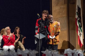 President Gayle Hutchinson (left) recognizes James Luyirika-Sewagudde, Jr., (right) for 45 years of service as staff are honored during the Staff Awards Luncheon in May 2018.