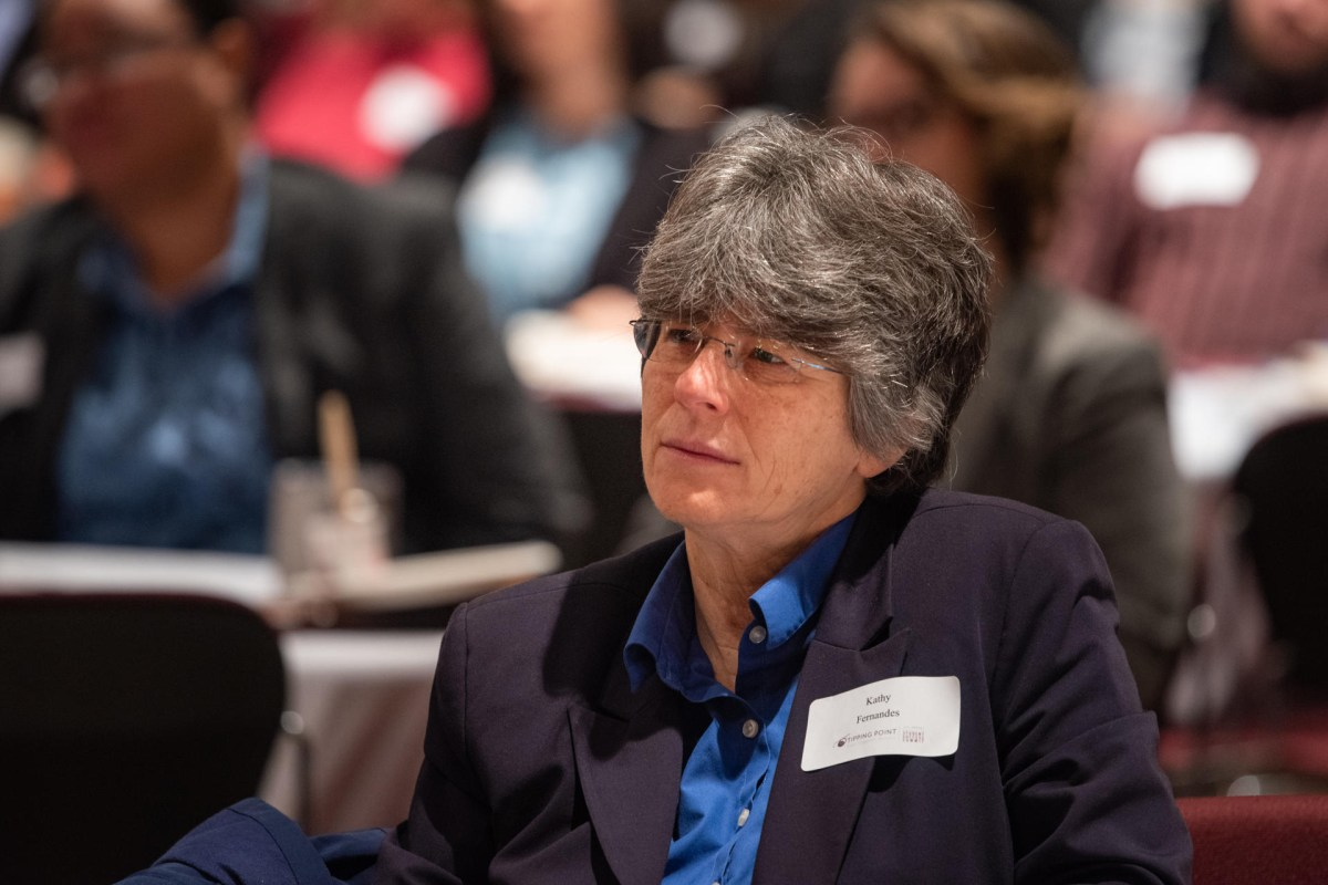 Kathy Fernandes sits and listens to someone speaking.