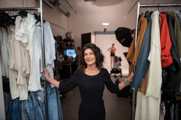 Debra Cannon stands between clothing racks while a fashion photoshoot takes place behind her.