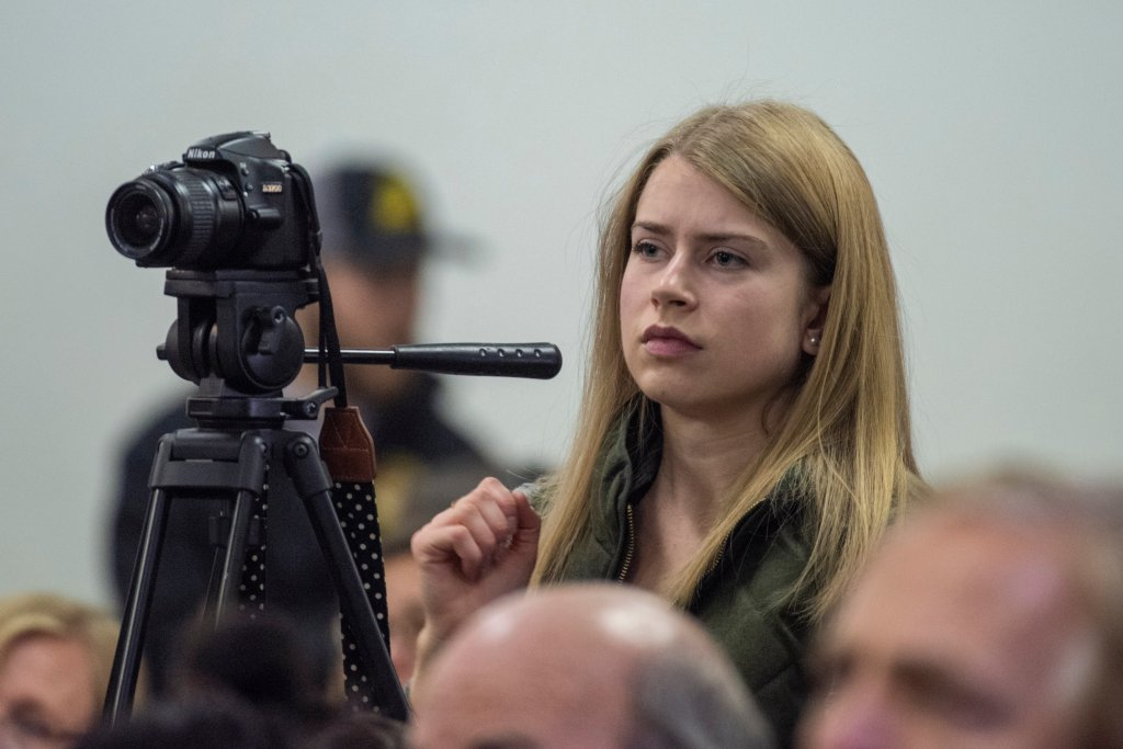 Olyvia Simpson looks through a video camera at a press conference.