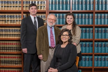 Program founder Edward Bronson with students who run the legal clinic, pictured behind legal text books.