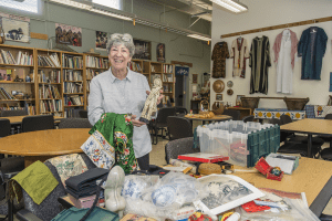 Sandy Shepard, director of RISE Library, sorts through boxes of donated artifacts. (Photo by Jason Halley)