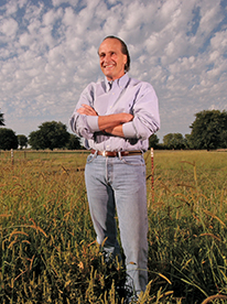 Dan Guistina with arms crossed and smiling in a green field at the University Farm
