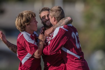 Three men's soccer players embrace in celebration after a game-winning goal.