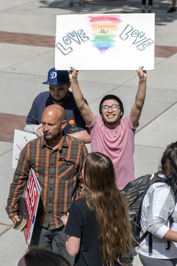 """Seve Christian (right) holds up a sign that reads """"Love is Love"""" as students speak back against persecution on campus from one man who only wanted to be identified as Ron (left), expressing the difference of opinions about religious views about Jesus Awareness Day on Wednesday, April 13, 2016 in Chico, Calif. (Jason Halley/University Photographer)"""