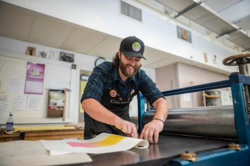Brett Day works on the print making press.