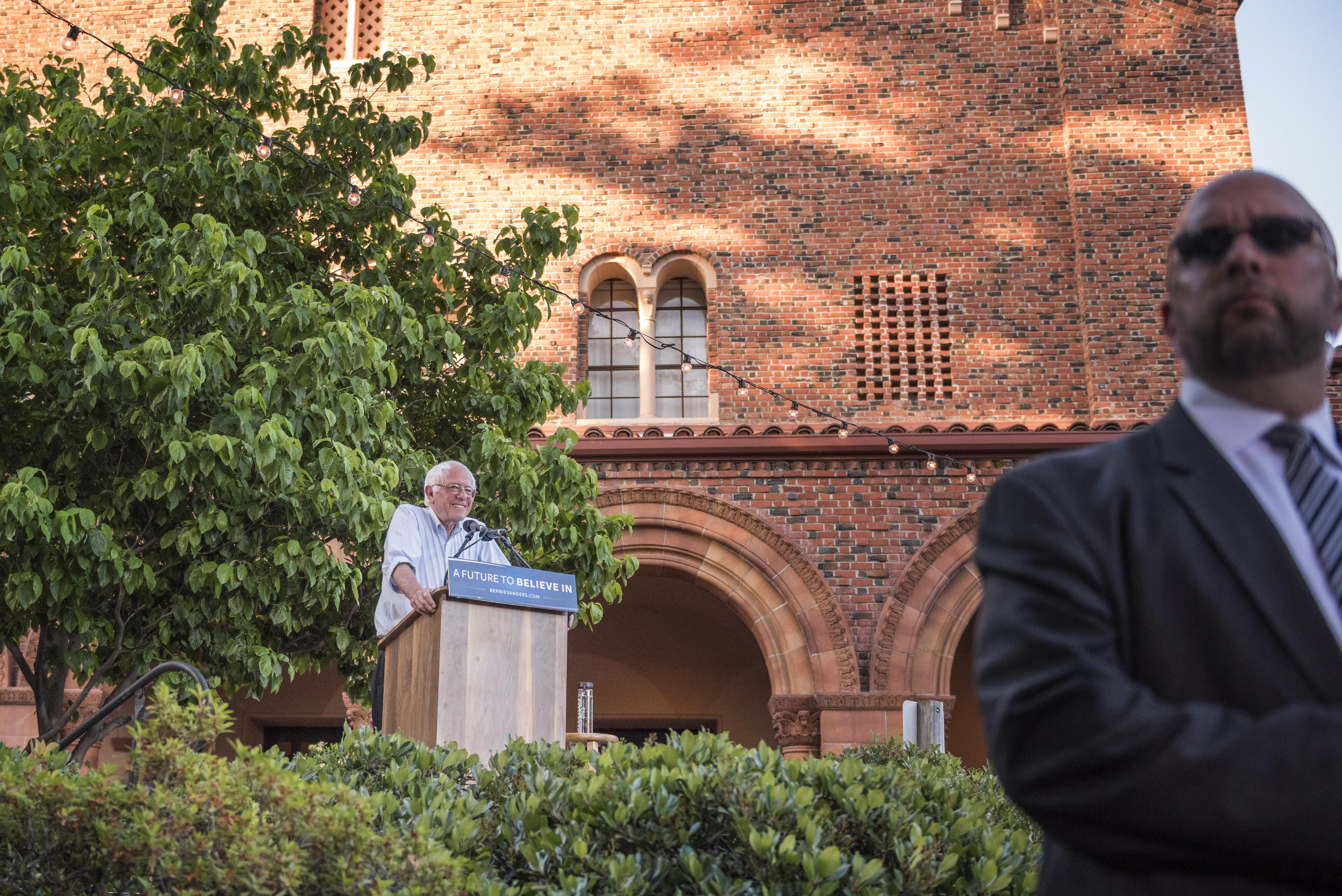 Bernie Sanders speaking at a podium in front of Laxson Auditorium.
