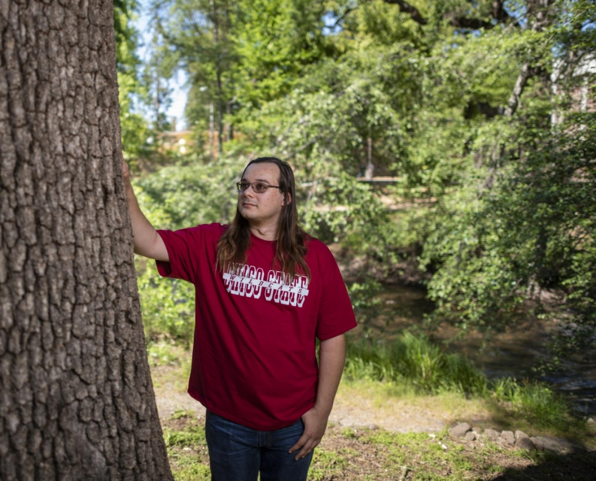 He-Lo Ramirez stands with his hand on a valley oak tree trunk near the waters of Big Chico Creek.