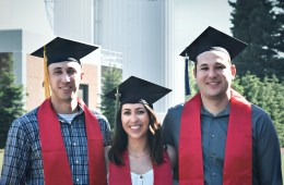 """Siblings Nick, Kayla, and AJ Gonzales wear their Chico State stoles as they stand in front of the boiler-chiller towers that say """"Chico State."""""""