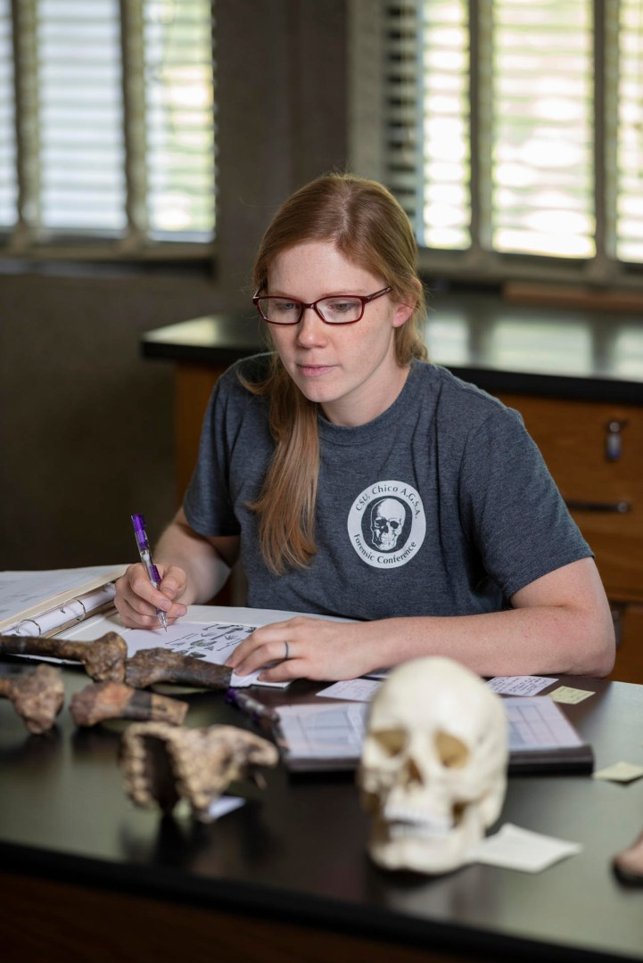 Jaqueline Galimany takes notes on a diagram of the human skeleton while looking at bone fragments on a table.