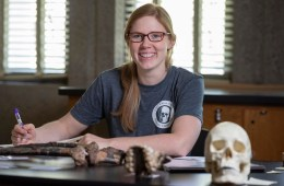 Jacqueline Galimany sits at a table with bone artifacts and a skull, prepared to take notes.