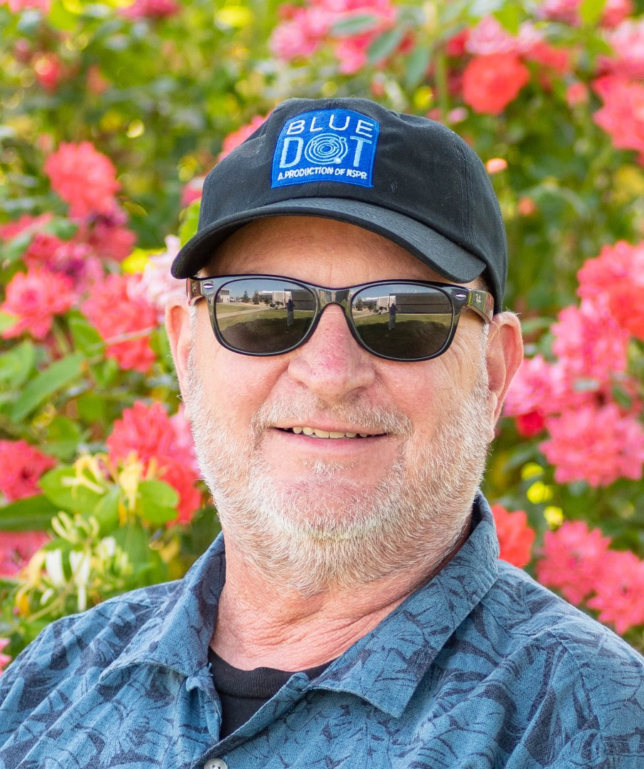 Dave Schlom wears a baseball cap and poses in front of colorful flowers.