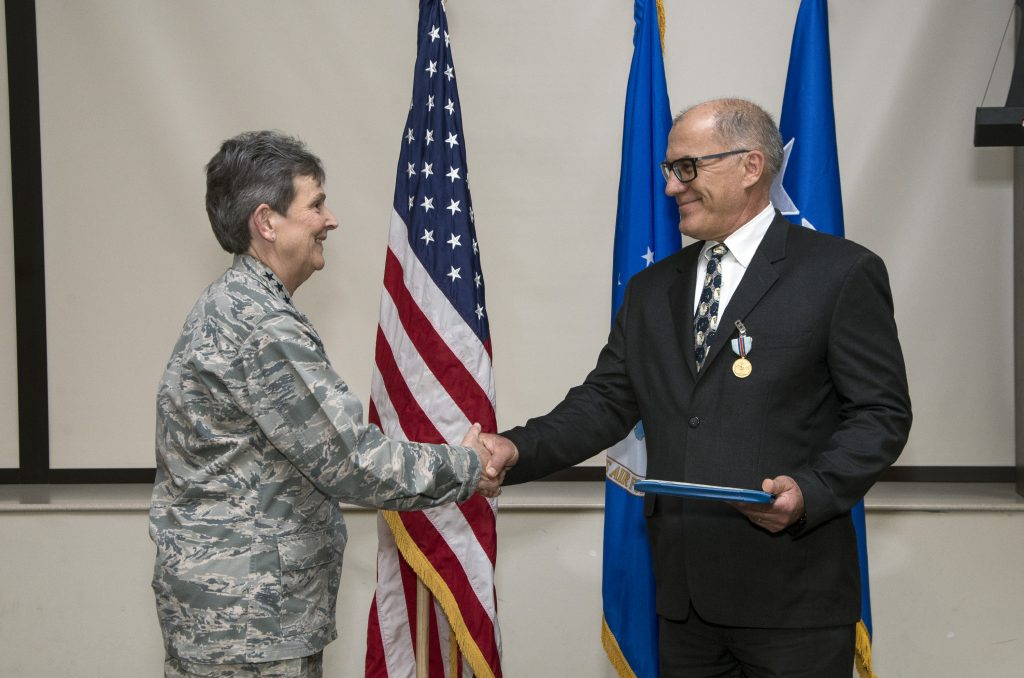 Gen. Ellen Pawlikowski shakes hands with Greg Gangnuss after presenting him with the Air Force Civilian Award for Valor.