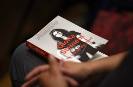 "A member of the audience hold Gloria Steinem's book, ""My Life on the Road."""