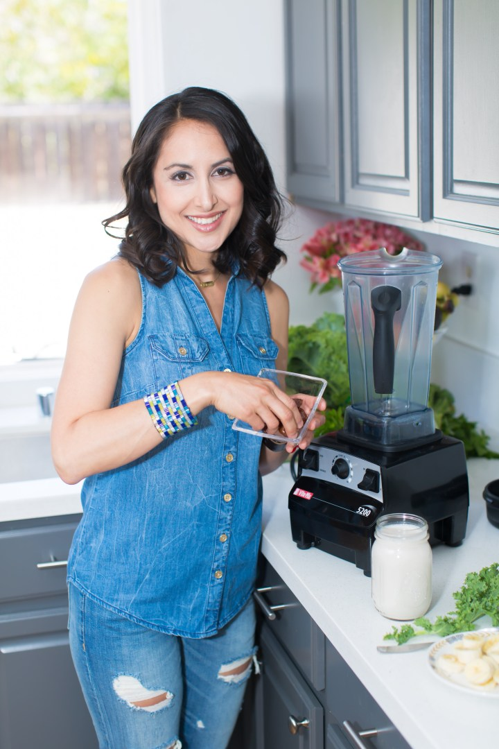 Brenda Sillas stands at a kitchen counter next to a blender, sliced bananas, kale, and dates.