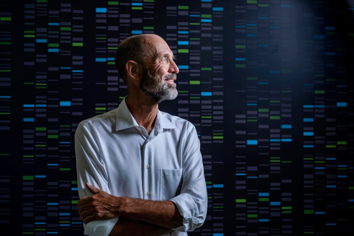 Portrait of Mark Velligan against a wall that shows the coding lines of DNA sequencing.