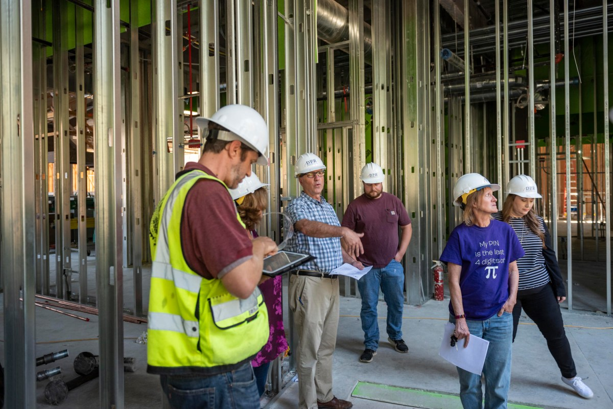 Randy Miller gestures as others in hard hats walk through the interior steel framed walls of the building.