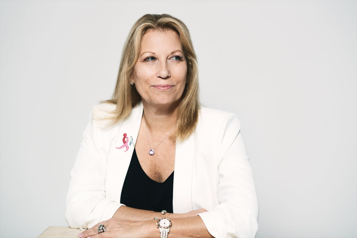 Portrait of Paula Schneider in a white blazer with pink ribbon lapel pin.